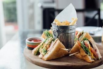 Sandwich et frites sur planche de bois