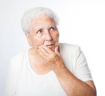 Senior femme inquiet avec la main sur le visage