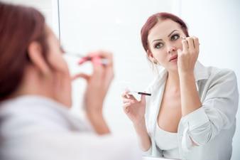 Sérieuse jeune femme appliquant une ombre à paupières au miroir