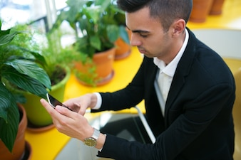 Serious busy businessman using smartphone for work