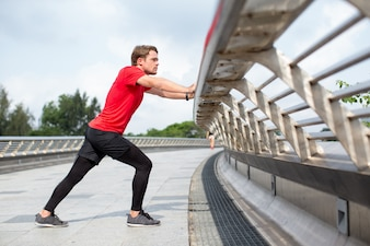 Serious Man Stretching Calf and Penching on Railing