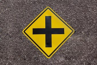 Signe d'intersection à l'avant sur fond de texture de route asphaltée