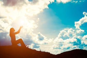 Silhouette de femme avec les mains levées