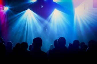 Silhouettes de groupe de rock sur scène au concert.