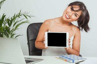 Smiley femme avec une tablette au bureau