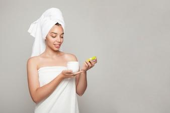 Smiley woman ouvre le produit cosmétique
