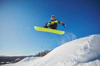 Snowboarder sautant à travers le ciel bleu