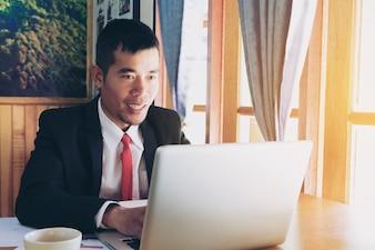 Souriant homme d'affaires assis à son bureau dans son bureau