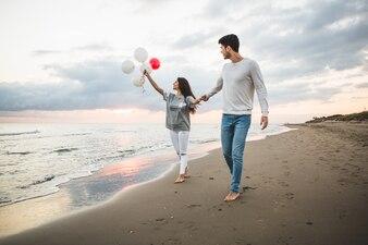 Sourire couple marchant sur la plage avec des ballons