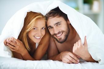 Sourire couple sous la couverture dans le lit