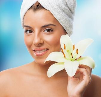 Sourire, femme dans une serviette avec une fleur de lys