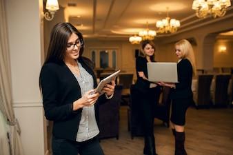 Sourire femmes offrant des affaires caucasiennes