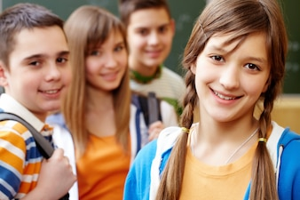 Sourire fille avec des camarades de classe derrière elle
