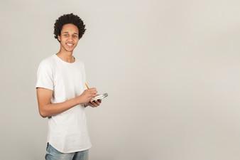 Sourire jeune homme prenant des notes