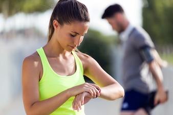 Sportive jeune femme à la recherche de son smartwatch dans la rue.