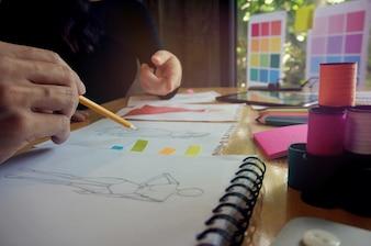 Stylish Fashion Designer travaille comme croquis de la nouvelle collection en atelier. Concept de conception créative