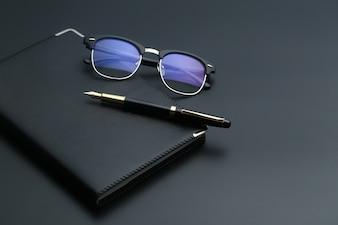 Stylo doré, cahier, calculatrice et lunettes sur bureau noir