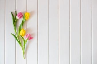 Surface blanche en bois avec de jolies tulipes