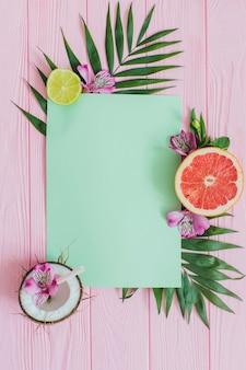 Surface en bois rose avec papier pour messages et fruits décoratifs
