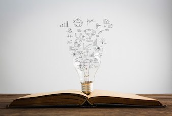 Symboles sortent d'une ampoule au-dessus d'un livre