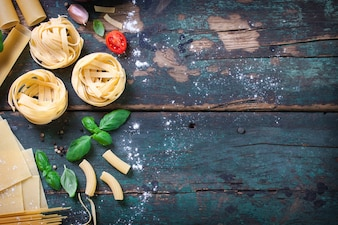 Table avec pâtes italiennes et des herbes aromatiques