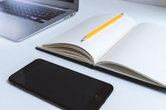 Table de travail au bureau avec ordinateur portable et smartphone