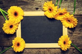 Tableau noir avec des fleurs jaunes autour