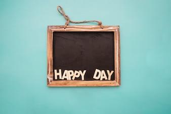 """Tableau noir avec le lettrage """"jour heureux"""""""