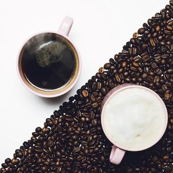 Tasses de café sur table blanche et tasse de lait sur table recouverte de grains de café