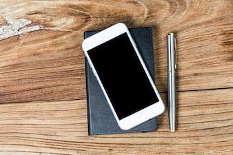Téléphone portable et écouteurs sur fond en bois
