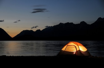 Tente éclairée dans la nuit à côté du lac