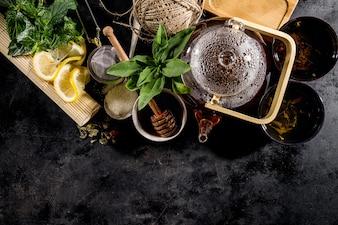Thé vert frais savoureux dans la cérémonie de théière en verre sur fond sombre au-dessus