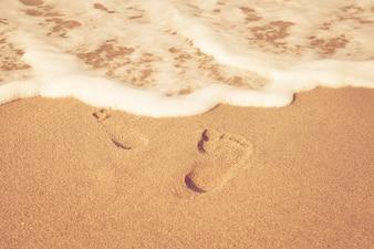 Timbre de pieds sur le sable sur la plage avec le soleil le matin, style de couleur vintage