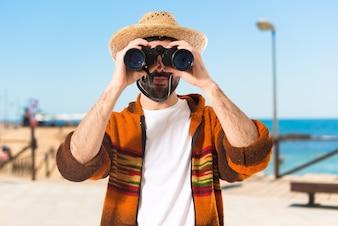 Touriste avec des jumelles sur fond blanc