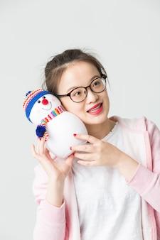 Tourné dans le studio de la jeune femme asiatique tenant un bonhomme de neige de Noël