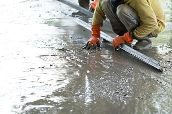 Travailleur de la construction déverse des planchers de béton, Construction de bâtiments sur le site avec de la main d'oeuvre, Concept de construction de maisons