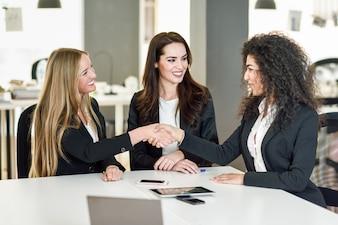 Trois femmes d'affaires se serrant la main dans un bureau moderne