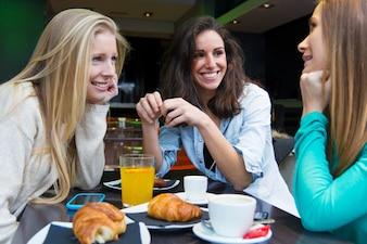 Trois jeunes amis prenant le petit déjeuner le matin en faisant du shopping dans la ville