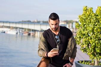 Un bel homme qui parle au téléphone à l'extérieur. Avec veste, sunglas