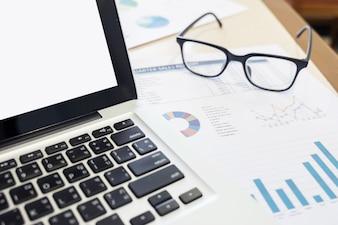 Un cahier, un ordinateur portable, des lunettes, une souris, une boussole vintage, une tasse à café, un stylo, un papier graphique (document) sur le bureau (table).