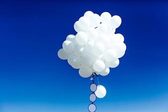 Un groupe de ballons blancs contre le ciel bleu le jour d'été.