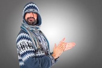 Un homme avec des vêtements d'hiver applaudissant sur fond gris
