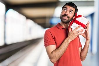 Un homme beau tenant un cadeau sur un fond non focalisé