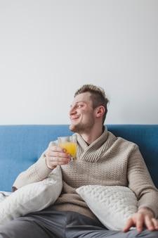 Un homme souriant au jus d'orange