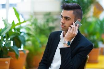 Un jeune entrepreneur pensif parle au téléphone
