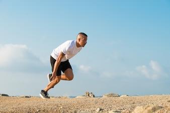 Un jeune sportif puissant commence à courir en plein air