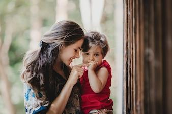 Un joli petit enfant tient le doigt de sa mère assis sur ses bras