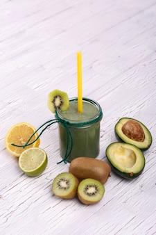Un smoothie sain avec de la citron vert, de l'avocat et du kiwi reposent sur la table