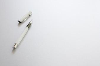 Un stylo blanc isolé sur papier d'écriture blanc, fond.