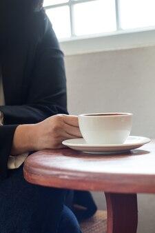 Une femme d'affaires tient une tasse de café blanc pendant le travail sur la table de bureau